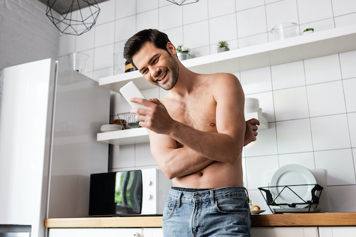 man reading and laughing at funny text message on his phone