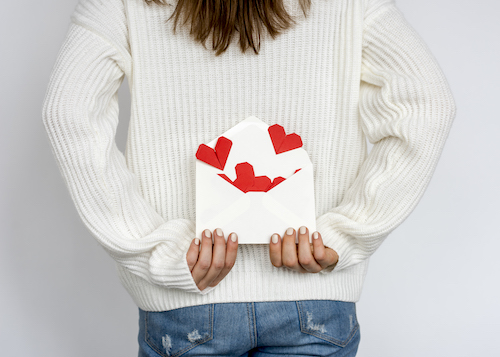 Woman holding envelope behind her back with small love messages for him. Love notes are in the shape of small red hearts.